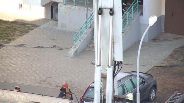 Hasič vběhne do vchodu s hasicím přístrojem, aby odstranil požár, záchranáři.,