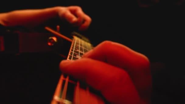 Muž hraje na kytaru prsty a struny zblízka. Multibarevné jevištní osvětlení, pozadí, zpomalení