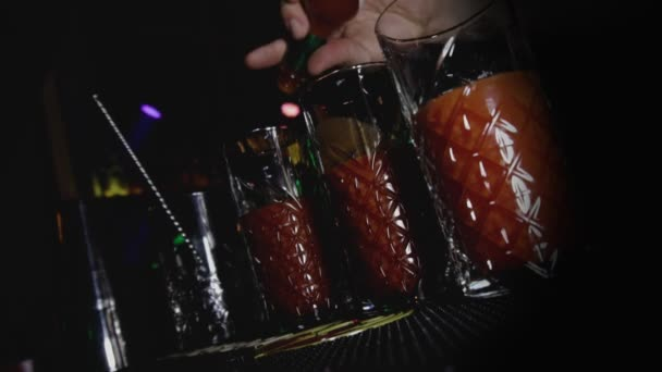 Barman fügt dem alkoholischen Cocktail Bloody Mary in einem Nachtclub scharfe Chili- oder Pfeffersoße hinzu. Junger Lebensstil und Erholung im Urlaubskonzept. Niederländischer Winkelschuss