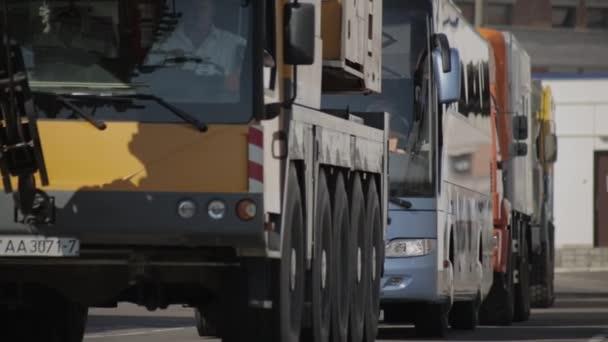 MINSK, BELARUS 08.05.16: Teleszkópos mobil daru Liebherr, személyszállító busz Mercedes, teherautó KAMAZ-4311, teherautó MAZ 6317, Gépjárműipari Rides City Street. Áruszállítás
