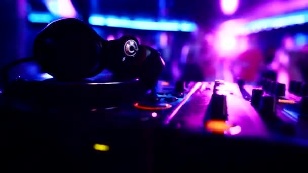 DJ music control panel with headphones on the background of dancing people in a nightclub, copy space