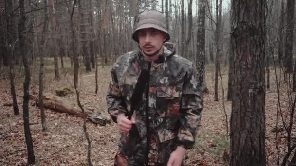 Furcsa tudósító mikrofonnal. A vadász erdőőr álruhába öltözve mond valamit a kamerának. 30 éves fehér férfi blogger bajusszal és borostával panama kalapban