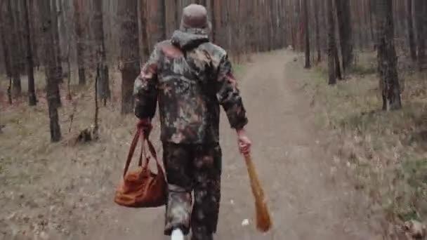 Vadász vadőr álruhába öltözve, táskával és seprűvel a kezében sétál az erdőben. Egy furcsa férfi Panama kalapban kimegy az ajtón. Kézifegyver mozgásban.