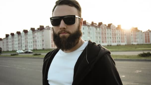 Brutal stylish man looks into a camera at sunset in city. Portrait of bearded modish vogue guy in black glasses. Fashionable trendy person with earring stands still in slow motion. Steadicam shot
