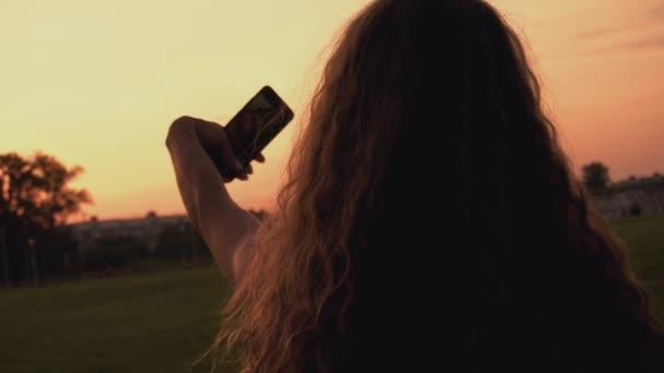 Langhaarige Bloggerin macht bei Sonnenuntergang ein Selfie am Telefon für ihre Follower oder Abonnenten in sozialen Netzwerken. Rückseite auf Rückseite. Vogue-Frau blickt in Smartphone-Kamera.