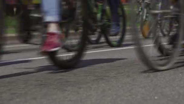 Cyklistický maraton. Hromadná jízda na kole ve městě. Závodní závod pro cyklisty. Občané s koly na hlavní třídě. Kolona sportovců. Nízký úhel záběru kol