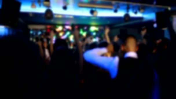 People wave their arms and hold light from flashlights in a nightclub, background, slow motion, stage for performance, blurry