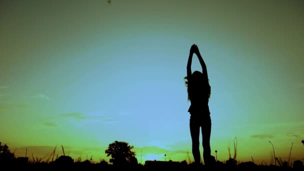 Hosszú hajú lány felugrik sziluettben naplementekor, lassított felvételben, sötét alakban. Szabadság koncepció. Profil, oldalnézet. Élvezet, nyaralás, pihenés. Parkolj a szabadban. Alacsony szögű széles lövés