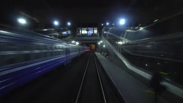 Timelapse train departs from passenger railway station at night. View from rear back window of last railroad coach carriage on rails in motion. Travel and tourism concept. Train pulls away