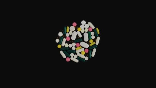 Mnoho pestrobarevných pilulek tablety tobolky s různými tvary leží na černém izolovaném pozadí. Koncept farmacie a medicíny. Léky pro zdraví. Věda. Horní pohled, kamera sklouzne dolů