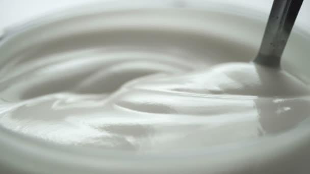 Makro - Videodreh, Zeitlupe des Mischens von Joghurt mit Löffel in der Tasse