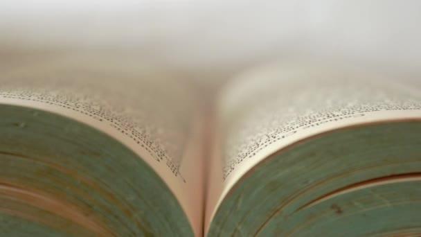 Die Hand der Frau öffnet langsam das alte Buch.