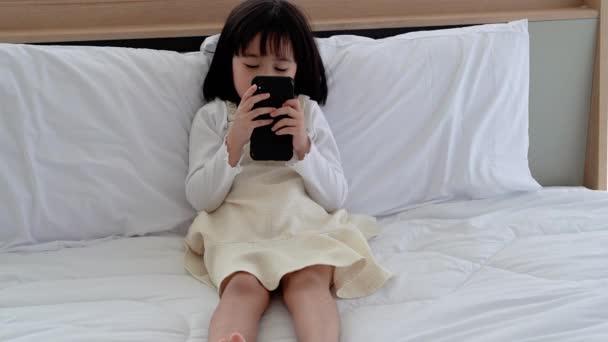 Lányok játszanak telefonon az ágyban, társadalmi problémák okozzák a gyermekek fejlődését.