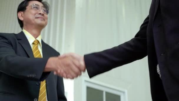 Starší asijský podnikatel potřást rukou, souhlasil se spoluprací