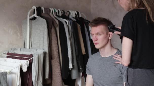 mladá žena řízne muže a omylem se dotkne jeho ucha s střihačem vlasů doma během izolace