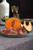 Melon and italian prosciutto on dark background