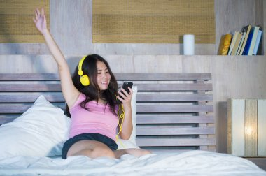 young attractive and happy Asian Chinese woman with yellow headphones listening to music in mobile phone on bed at home smiling having fun