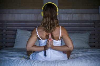 indoors back portrait of beautiful and fit healthy woman 30s practicing yoga in bed  calm and relaxed concentrated in meditation namaste pose