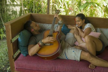 young beautiful and happy mixed ethnicity couple in hipster style chilling outdoors playing guitar relaxed at tranquil garden enjoying holiday retreat together in love