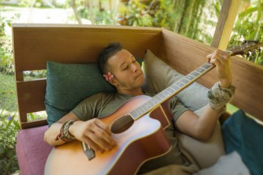 young handsome and happy mixed ethnicity man in hipster style chilling outdoors playing guitar relaxed at tranquil tropical garden enjoying holiday retreat