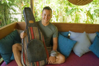 young handsome and happy mixed ethnicity man in hipster style chilling outdoors with guitar relaxed at tranquil tropical garden enjoying holiday retreat