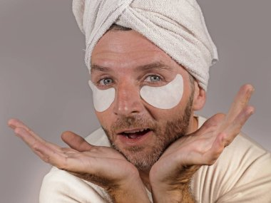 funny isolated face portrait of young happy and attractive camp homosexual man  applying moisturizer eye patch facial product with head wrapped towel in masculine skincare