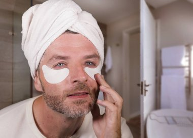 funny face portrait of young happy and attractive camp homosexual man  applying moisturizer eye patch facial product with head wrapped towel in masculine skincare and soft beauty concept