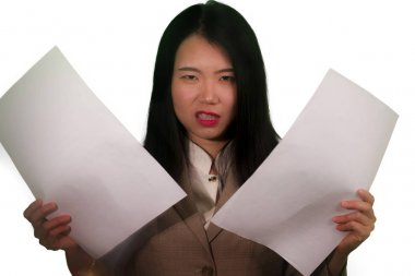 business stress portrait of young attractive upset and stressed executive Asian Korean woman tired and unhappy holding paperwork overwhelmed in furious face expression