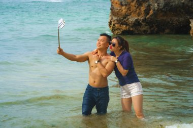 Summer holidays lifestyle portrait of young happy and playful Asian Chinese couple enjoying at the beach taking stick selfie photo with hand phone enjoying sea together