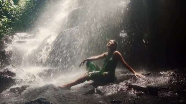 slow motion on young attractive Asian Indonesian woman in sarong overwhelmed by the beauty of waterfall in Bali tropical jungle letting water falling on her feeling free and blissful