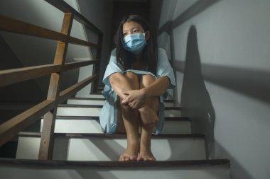 Korkak ve endişeli Koreli Koreli bir kadının hüzünlü portresi. Ev kilitlenmesi ve karantina sırasında dramatik bir ışık altında virüsler salgını sırasında merdivenlerde oturuyor.