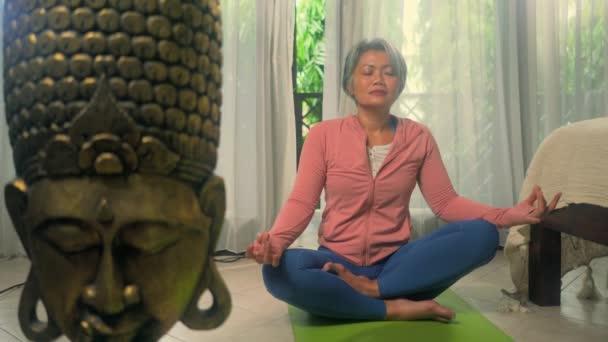 home lifestyle - krásná a šťastná zralá žena s šedivými vlasy na její 50s dělat jógu a meditační cvičení na asijské deco ložnice pocit klidu a rovnováhy ve wellness a zdravého stárnutí