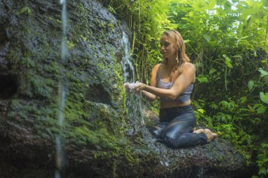 outdoors adventure portrait of young beautiful and happy woman in rock at tropical rainforest playing with water fresh and carefree enjoying nature during Summer holidays trip
