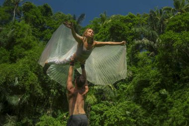 yoga workout - young attractive and happy couple doing acroyoga at tropical green forest enjoying nature the girl spreading wings flying hold by man in healthy lifestyle and fitness