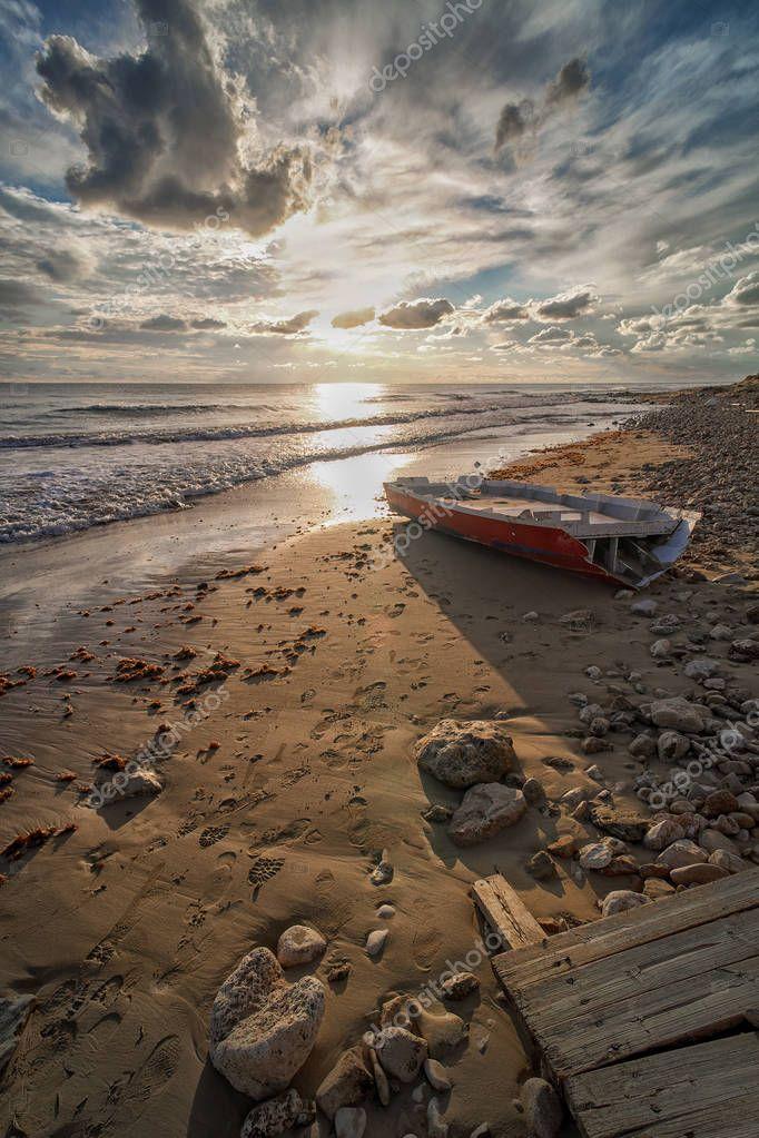 Spiaggia del Salento al tramonto,con barca.