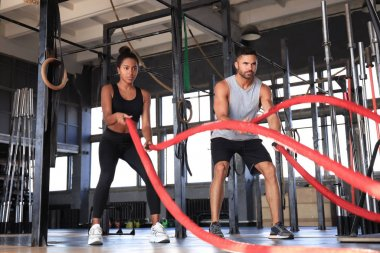 Athletic young couple with battle rope doing exercise in functional training fitness gym.