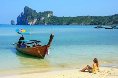 Young woman sitting at Ao Loh Dalum beach on Phi Phi Don Island,