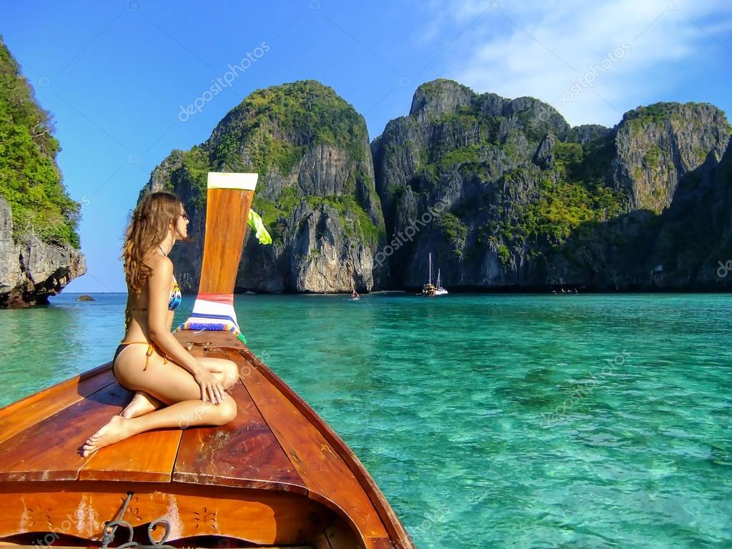 Young woman sitting at the front of longtail boat in Maya Bay on
