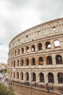 ROME, ITALY - 10 MARCH 2018: Colosseum ruins with tourists passing by on cloudy day stock vector