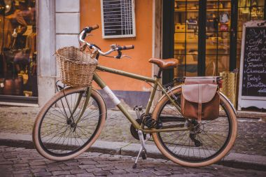 ROME, ITALY - 10 MARCH 2018: bicycle standing in front of store on street of Rome stock vector