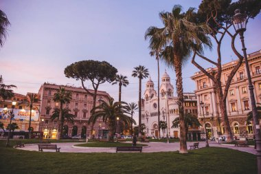 ROME, ITALY - 10 MARCH 2018: palm trees in square at Rome in evening