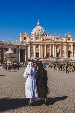 VATICAN, ITALY - 10 MARCH 2018: nuns walking by St. Peter's square on sunny day stock vector