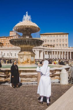 VATICAN, ITALY - 10 MARCH 2018: nuns taking photo in front of Maderno fountain on St. Peter's square stock vector