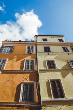 bottom view of ancient buildings on street of Rome on sunny day, Italy