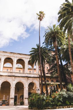 beautiful ancient atrium building with palm trees on foreground, Rome, Italy