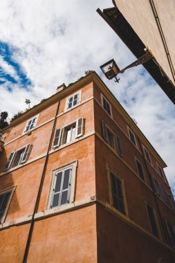 bottom view of ancient building on street of Rome on cloudy day, Italy