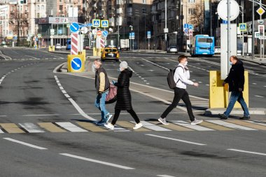 Covid-19, quarantine in Moscow, coronavirus in Russia. People in protective medical mask crosses the road during self-isolation.