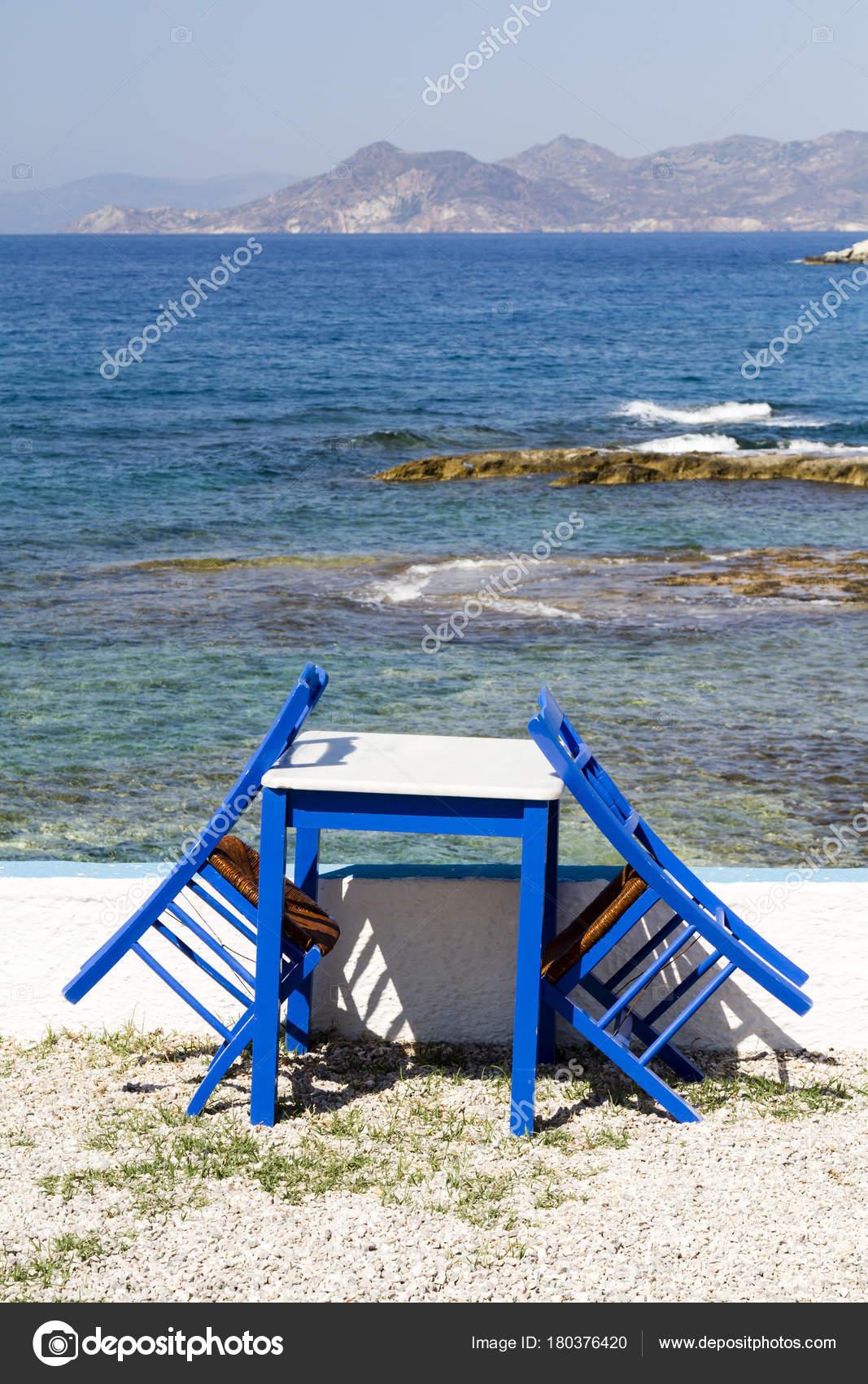 Bemalte Stühle bemalte stühle und tisch am meer stockfoto tonytaylorstock