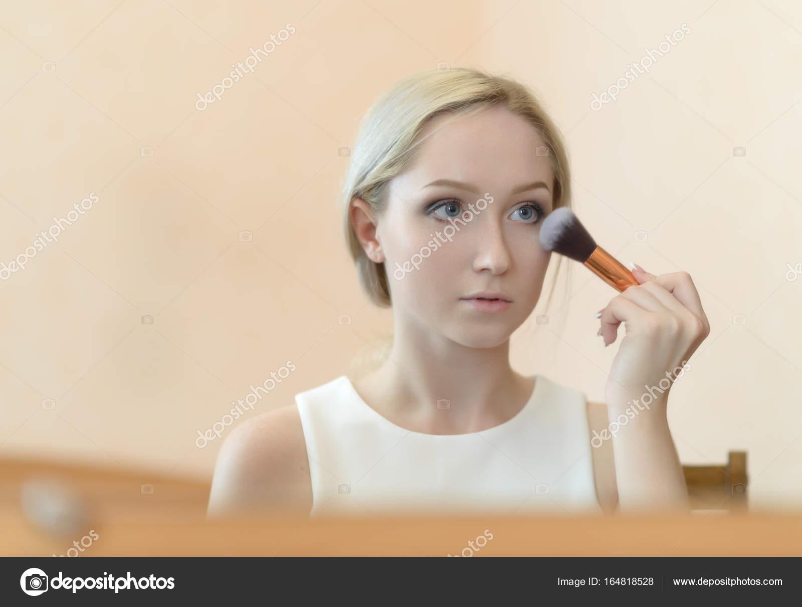Mujer mirando en el espejo mientras se aplica el maquillaje — Fotos ...