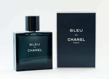 VLADIVOSTOK, RUSSIA - DECEMBER 4, 2017: A bottle of Bleu De Chanel perfume on a light background. Chanel S. A. - French company for the production of clothing and luxury goods, founded by fashion designer Coco Chanel in Paris in the early XX century.